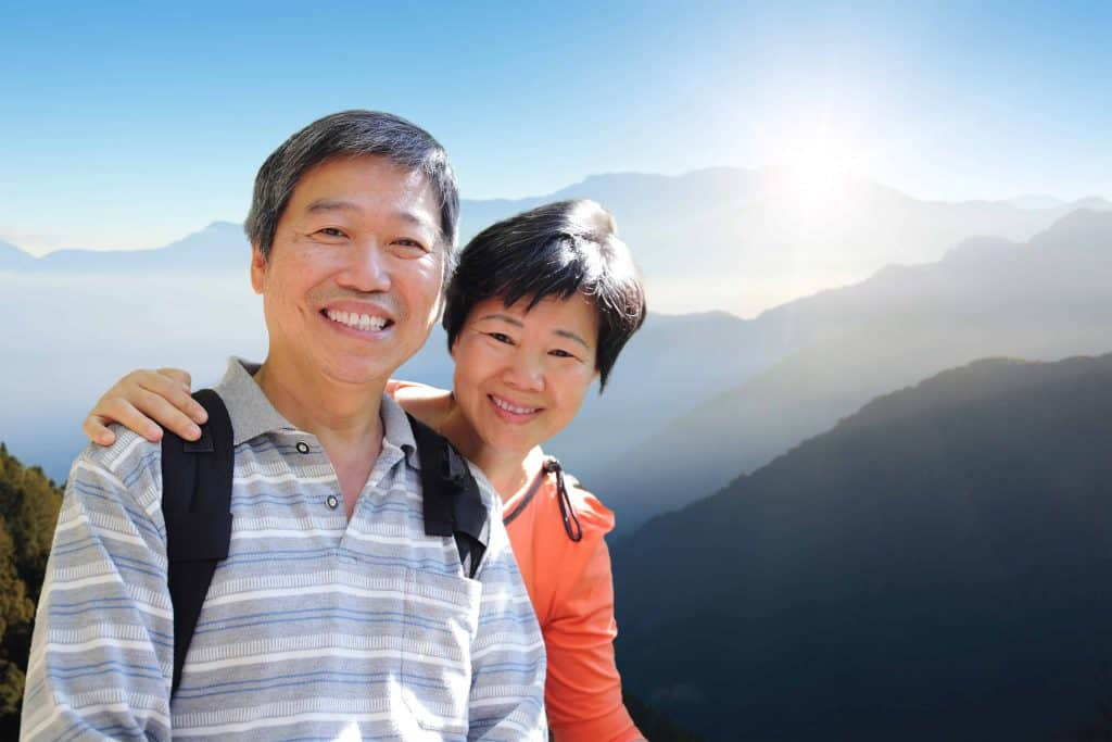 Asian couple hiking with mountain view
