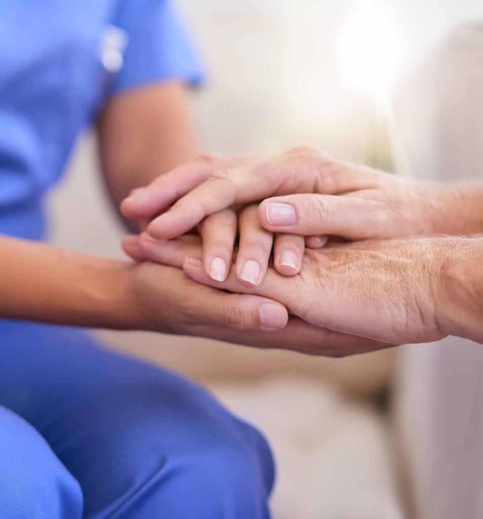 nurse holding senior's hand